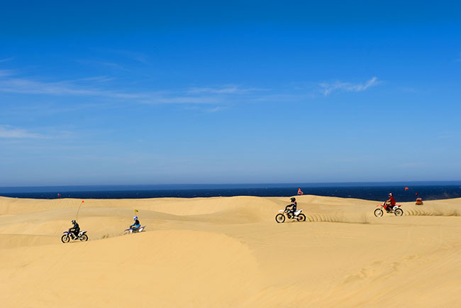 Four dirt bikes riding on the dunes