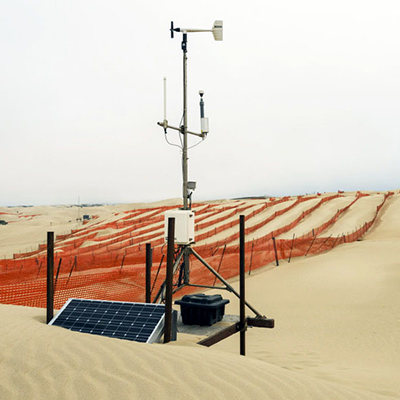 Image of sand dune, weather station, and orange wind fencing