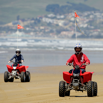 image of two red quads and riders on the beach with ocean in the background